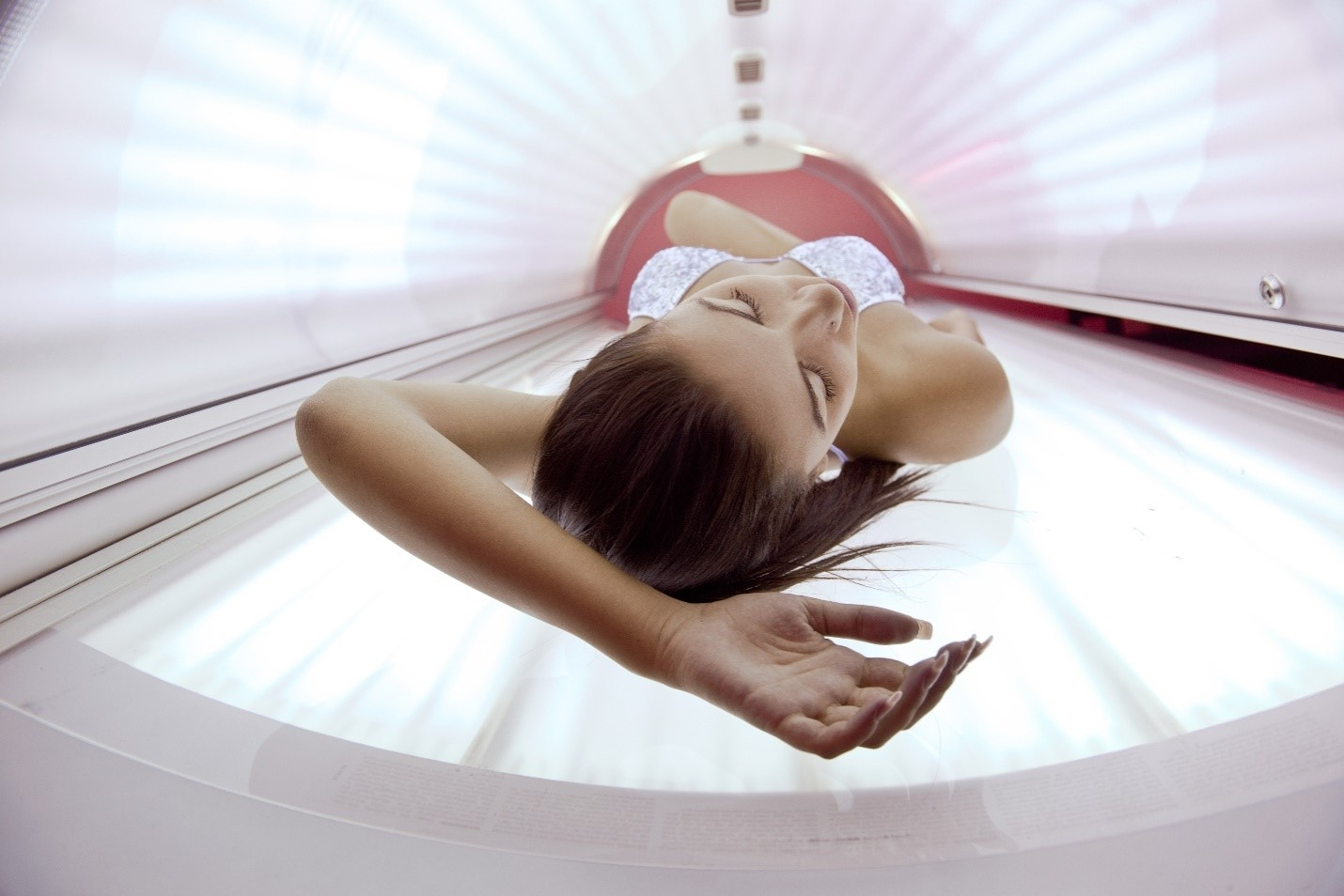 A young woman lying in a tanning bed