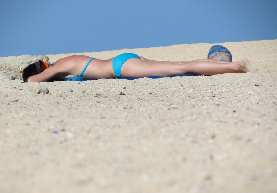 A woman lying on a beach while working on her tan.